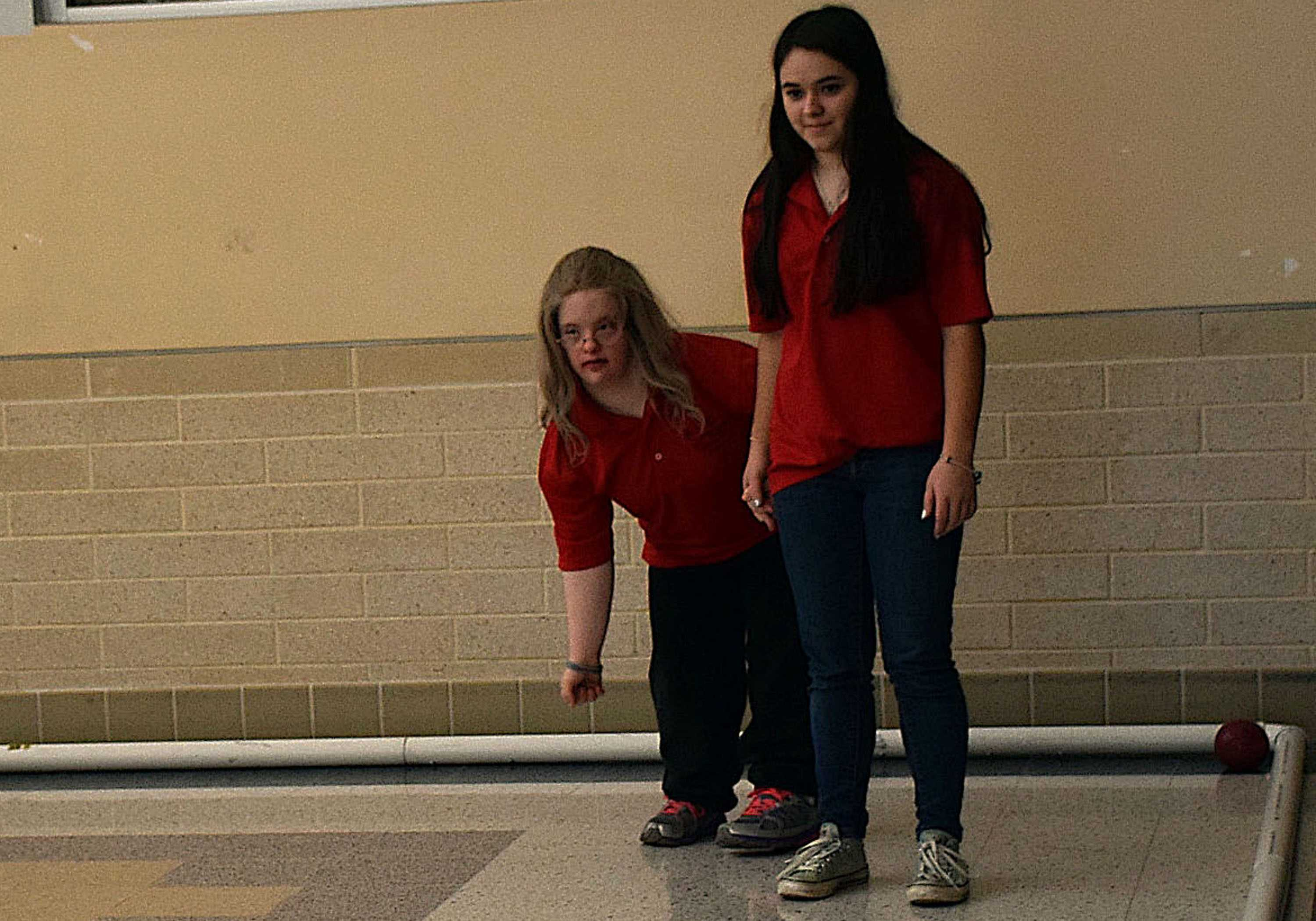 Michelle Weddle (right) helps Sarah Webber (left) throw the bocce ball at their match against Oakdale.