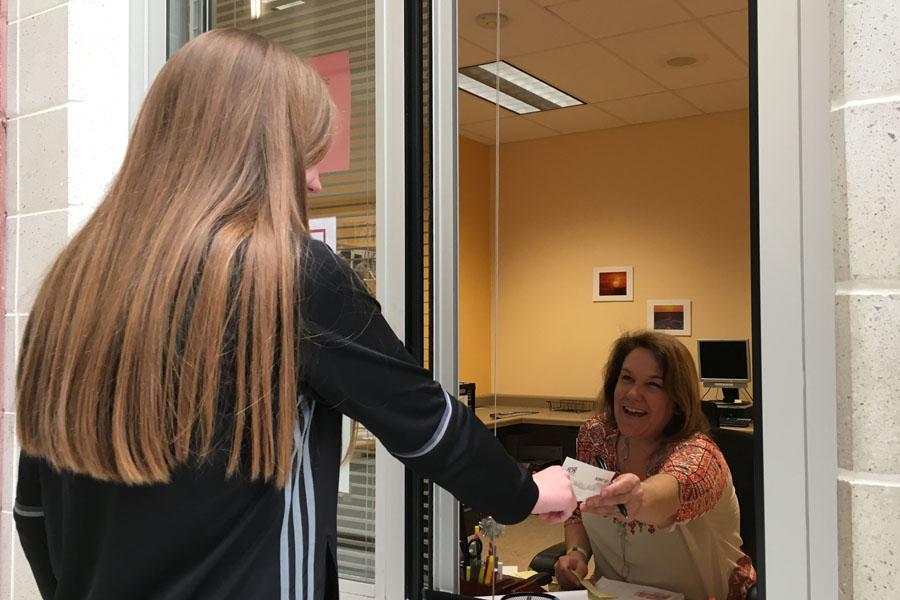 Mallory Maher receives a slip from attendance secretary Jennifer Twiford.