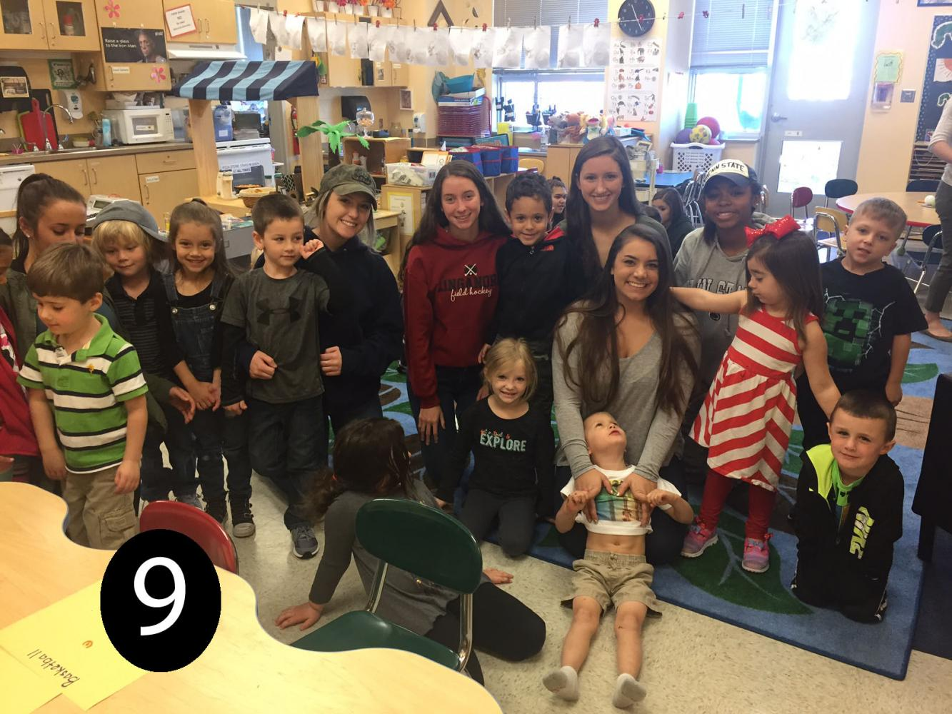 The seniors in the Child Development class pose with some of the preschoolers.