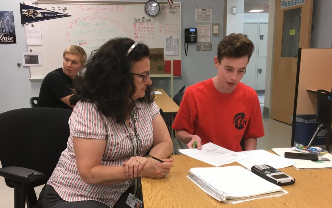 Mary Jo York assists Jake Bolger with his mathematics schoolwork.