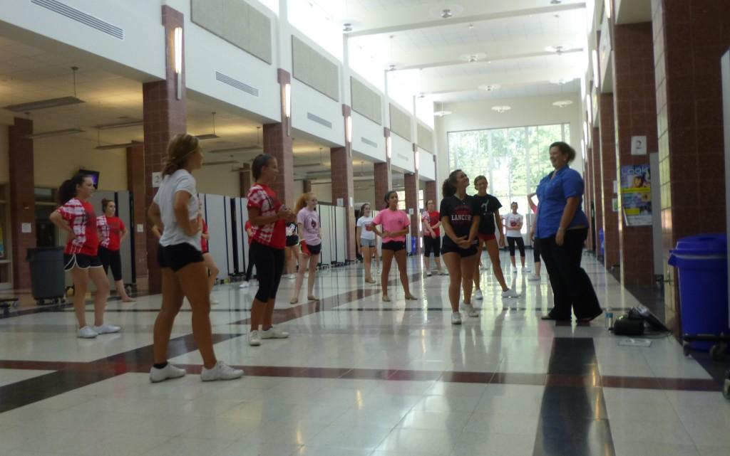 The poms team practices in the cafeteria.