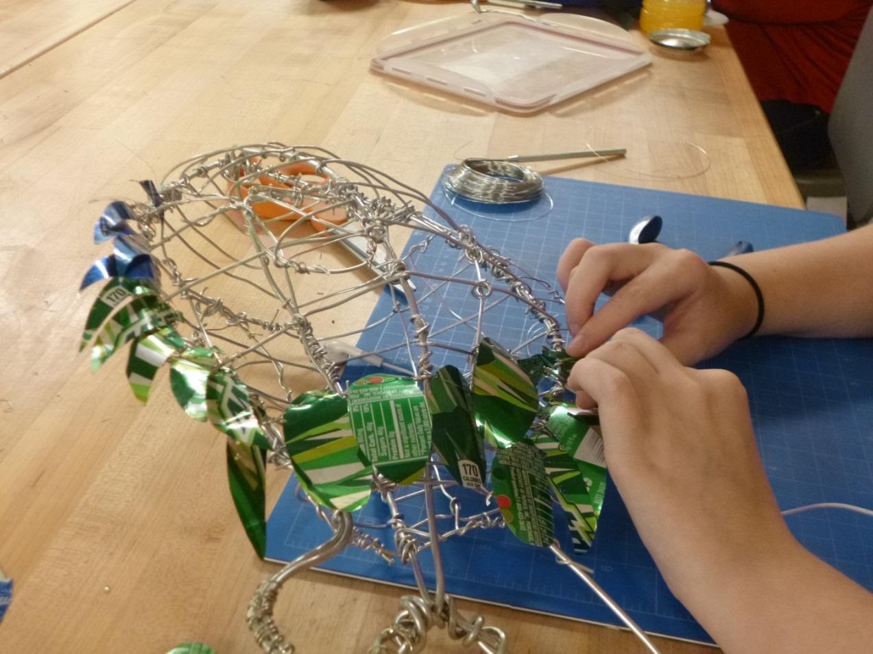 Mariah Wilson, 11th grade, creates bird sculptures out of wire and soda cans.  Photo Courtesy of Rachel Cleveland, 12th grade.