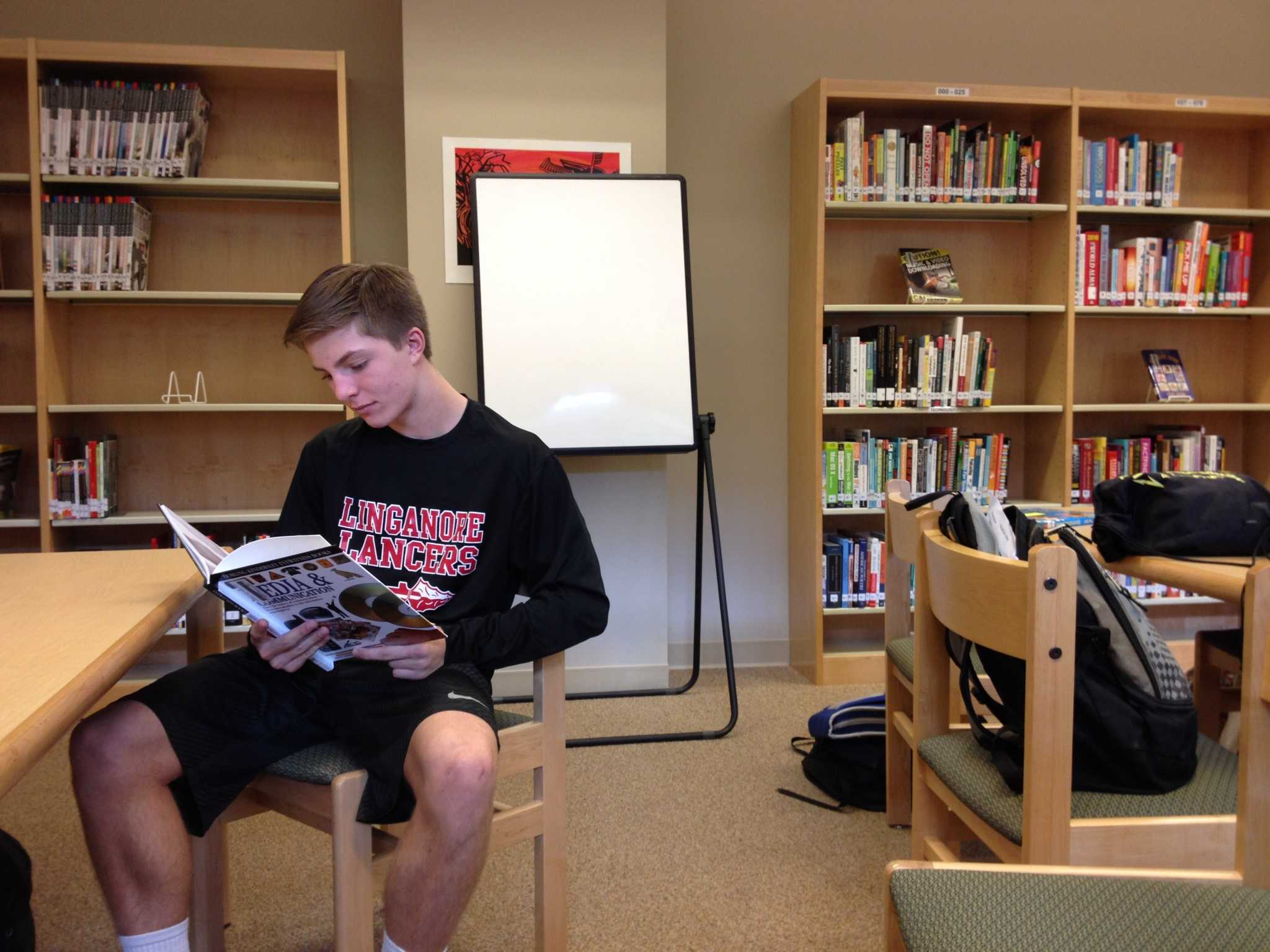 Freshman Jac Medve studies in the media center third period.