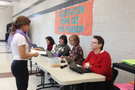 Junior Olivia DuBro hands in her registration form during third lunch on Thursday.