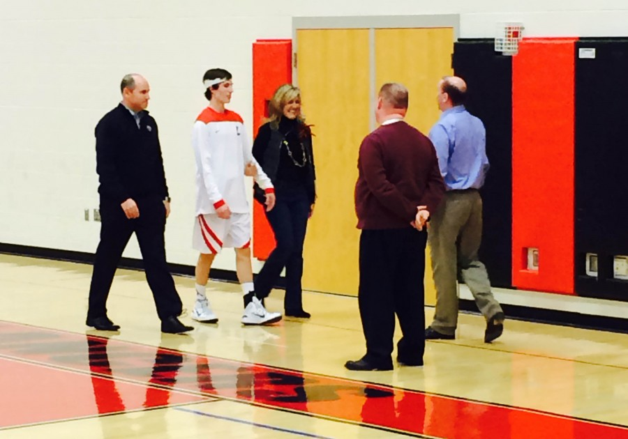 Senior Evan Rowan is escorted by his parents during senior night for the boy's basketball team.