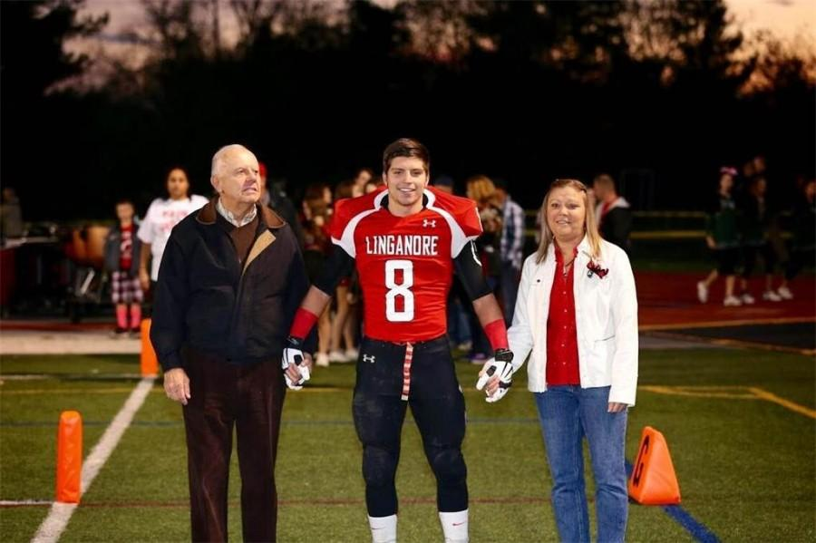 Casey Alvarado poses with his mother Cindy for a photo on the football field on senior night.