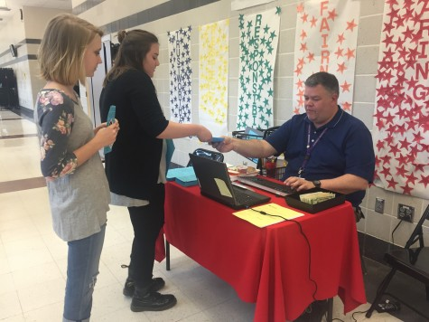 Mr. Brown sells prom tickets to seniors Olivia Goldstein and Izzy Peterson during third lunch.