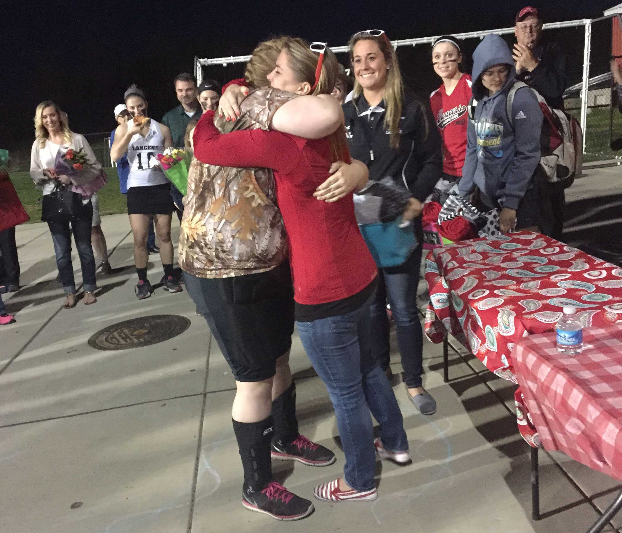 Taylor Wheelock hugs coach Jackie Sowers at the end ceremony on Senior Night