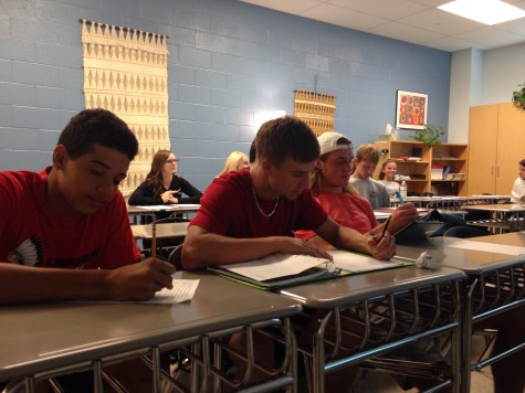 Three senior varsity football players Gary Raney on the left, Ian Faulconer in the middle, and Wade Stieren all participating in their AP composition class.