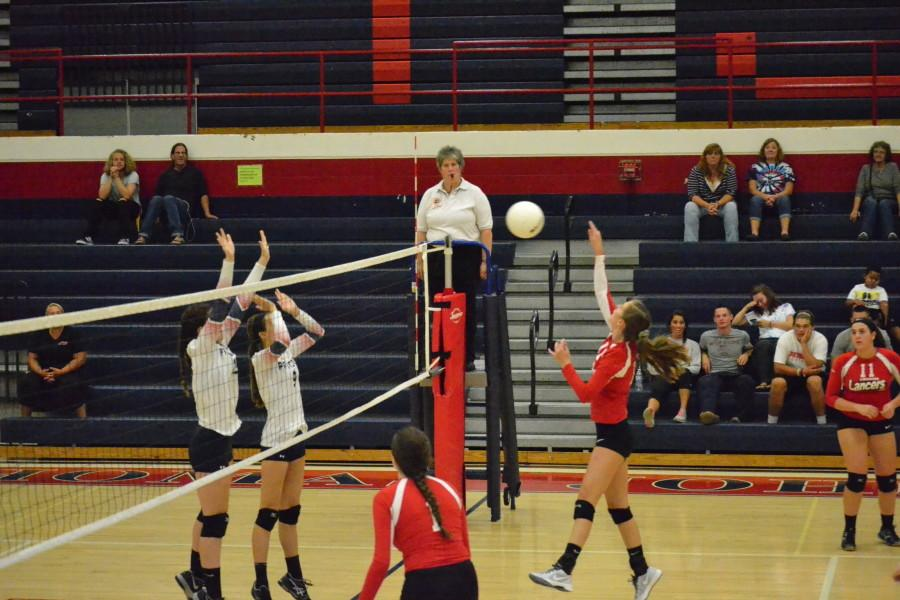 Junior Claire Coupard (16) prepares to hit the ball over the net, while junior Eva Rowan (1) and sophomore Maddie France (11) are close behind.