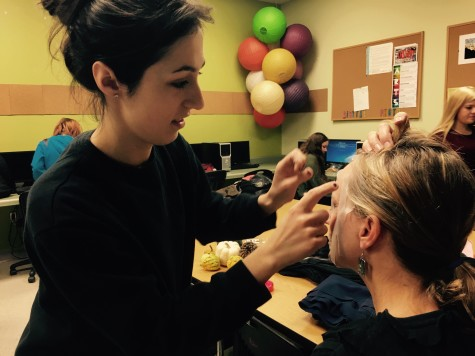 Gina DeFrancisci applies tape to Mrs. Rebetsky to prepare for a tape portrait.