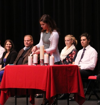 National Honor Society secretary Olivia DuBro lights candle.