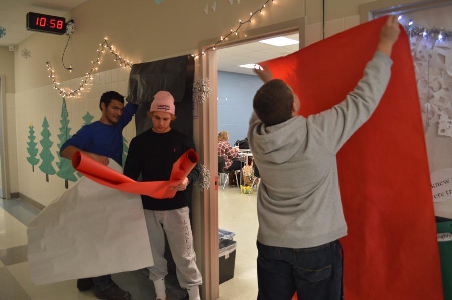 Seniors Alex Martinazzi, Tyler Loveless, and Connor Gottfeld prepare the classroom door.
