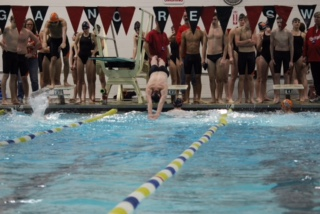 Senior Jake Butehorn dives over Sophomore Michael Roach in the Boys 200 Medley Relay.
