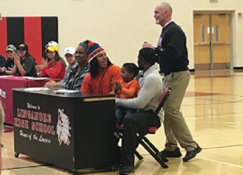 Surrounded by family, Dante Butler listens to Coach Rick Conner speak before signing his National Letter of Intent.