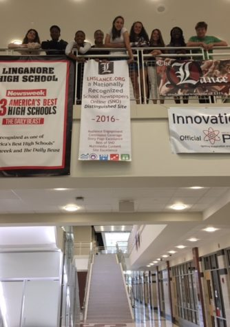 Staff members triumphantly hang the banner.