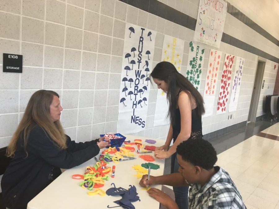 Class of 2019 member, Jackson Ambush, and Class of 2017 member, Emily Nemeth, participate in the LHS Character Counts wall with the help of Ms. Aburto.