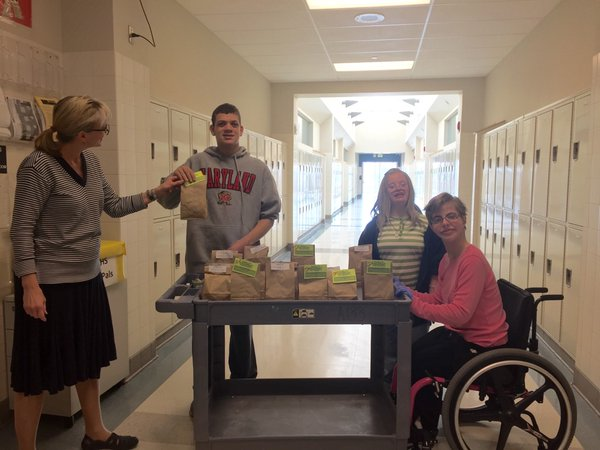 Learning for Life students John Paul Beall, Sarah Webster, and Suscha Campbell deliver a bag of popcorn to Mrs. Rebetsky