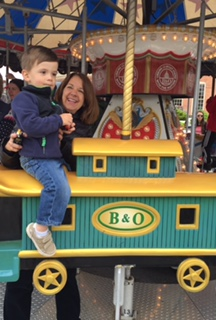 Principal Doll with her grandson  on a carousel.