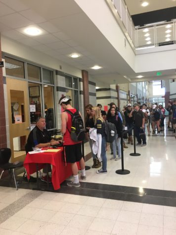 Students buy tickets for the homecoming dance from Mr. Brown.