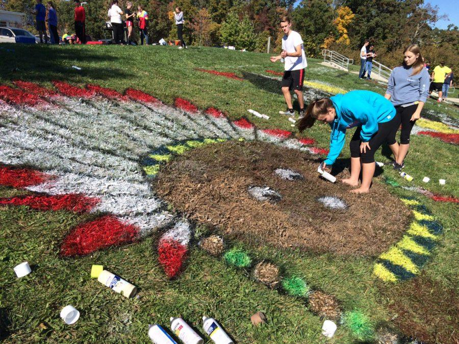 Class of 2018 students, Josh Watson and Delaney Krotz, spray painting an Indian on their part of the hill for the Homecoming Hill painting in 2015.