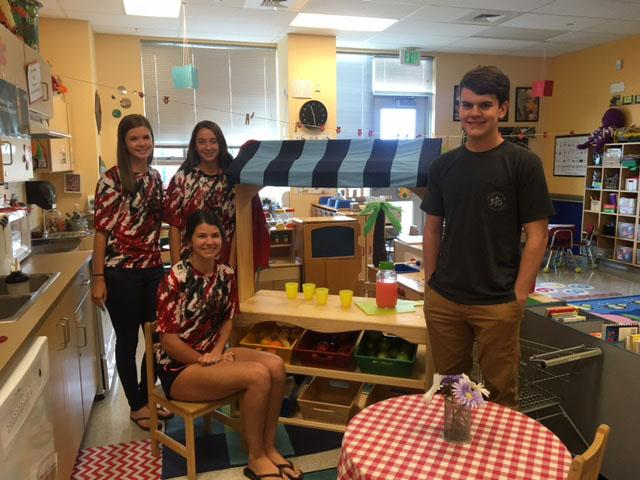 Wolfe's daughters, Olivia, Gabriella, and Emily,  gather at the lemonade stand  with Justin Kleinmann.