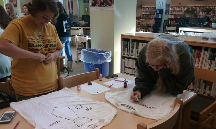 Frannie Davis and Megan Warren use fabric markers and puffy paint to draw on their shirts.