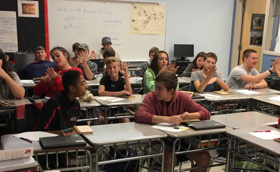 Mrs. Rebetsky's English 9 study their palms and try to guess their futures based on the lines.