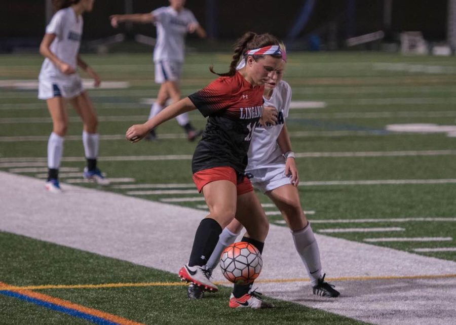 Mid-fielder, Ashley Yurich, fights for the ball .