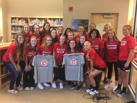 Varsity Girls Soccer team shows off Miranda Keaton's new shirts and award.
