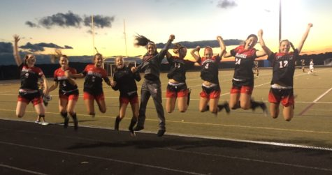 The girls varsity team jump in victory.