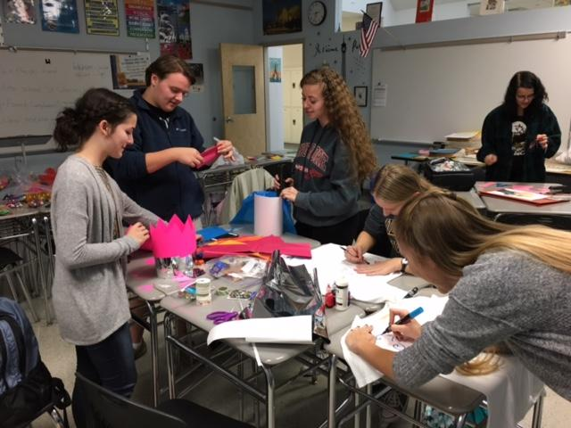 Sofia Schuller, Paul Servary, and Morgan Harris, all class of 2018, make paper hats in celebration of St. Catherine's Day.