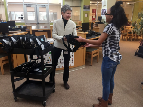Marsha Thompson distributes a Chromebook to student, Sylvia Nelson