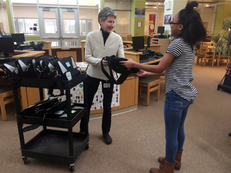 Marsha Thompson distributes a Chromebook to student, Sylvia Nelson