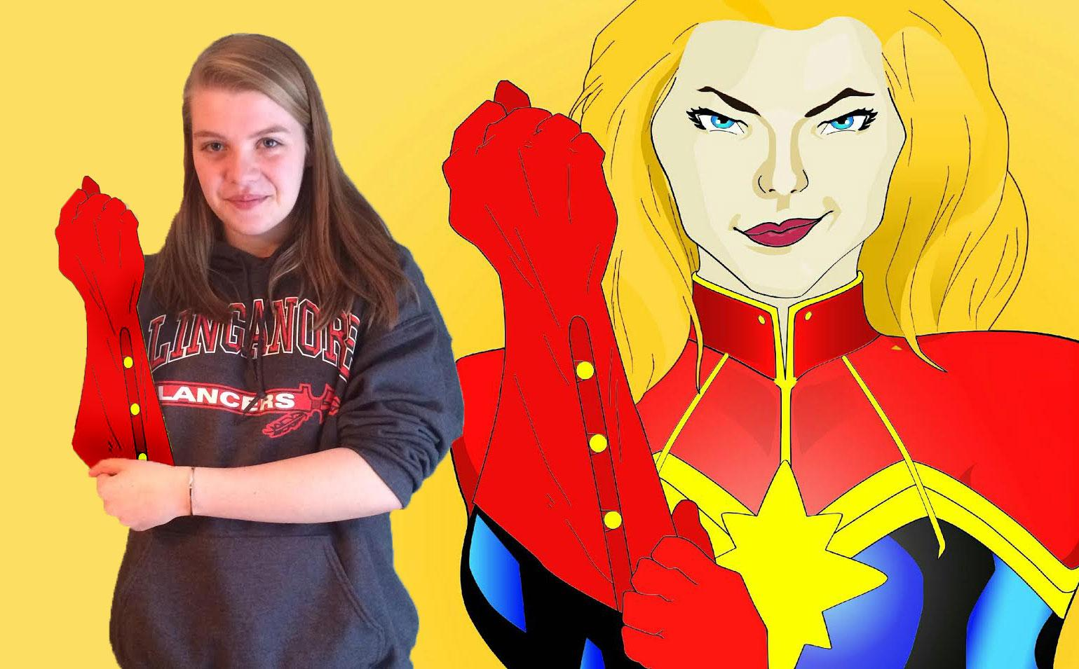 Sophie the Super-artist poses next to one of her superhero graphics.