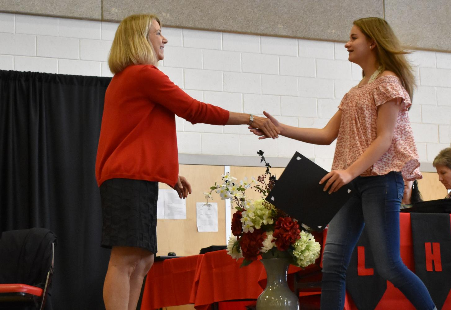 Lexi Fowler shakes hands with Principal Nancy Doll.