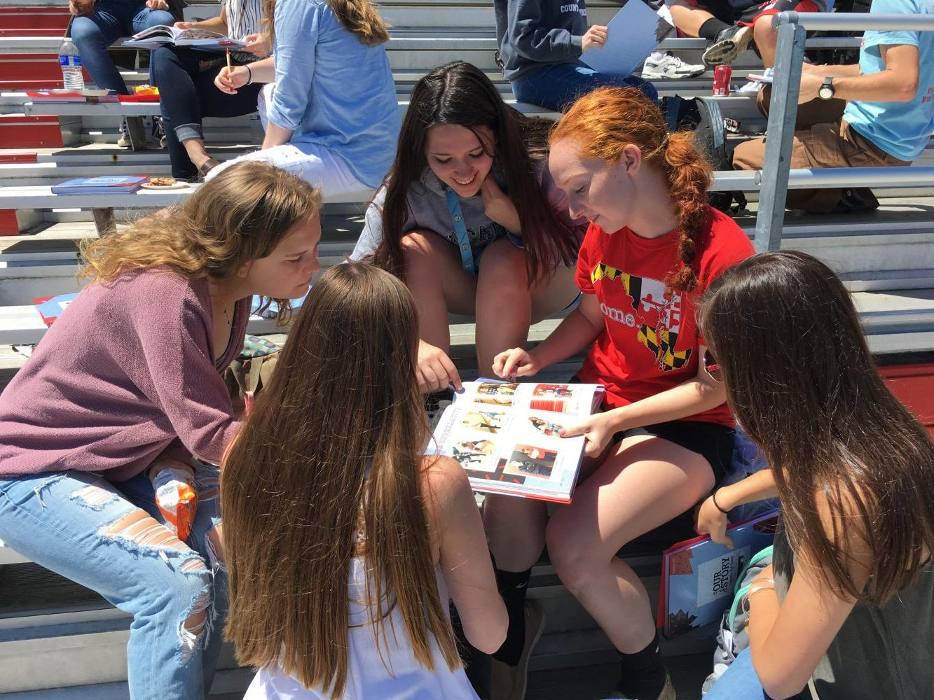 Valerie Coblentz, Brooke Bennett, Kassidy Ferris, Miranda Timberlake, and Courtney Green (left to right) look at the 2016-17 yearbooks