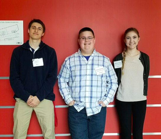 Evan Hooper, Madison Reeley, and Patrick Stalnaker pose by the wall