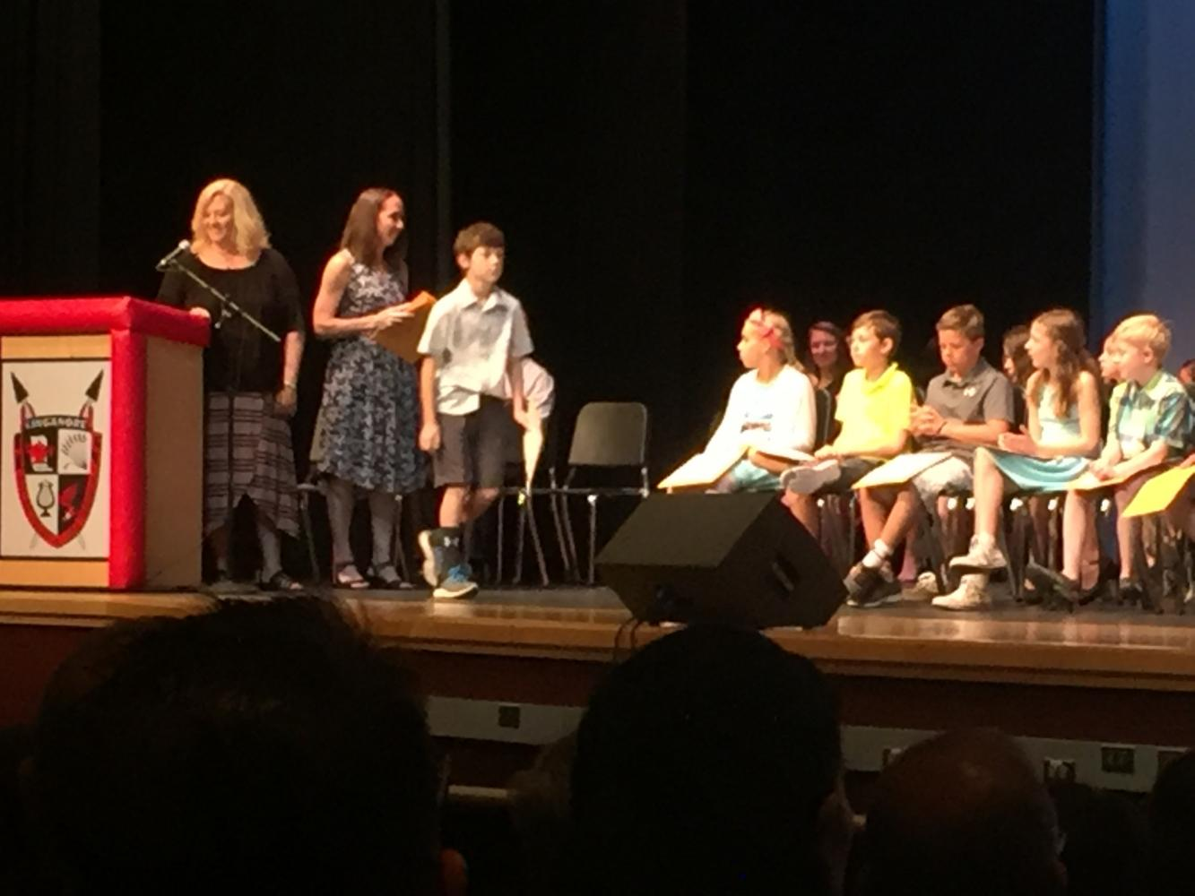 Fifth grader John Lehman receives his graduation certificate.