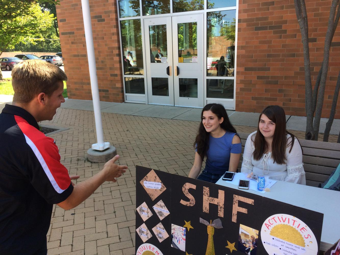 SGA president Jack Dubro talks with French Honor Society president Sophia Schuller and vice president Olivia Hubble about joining their club.