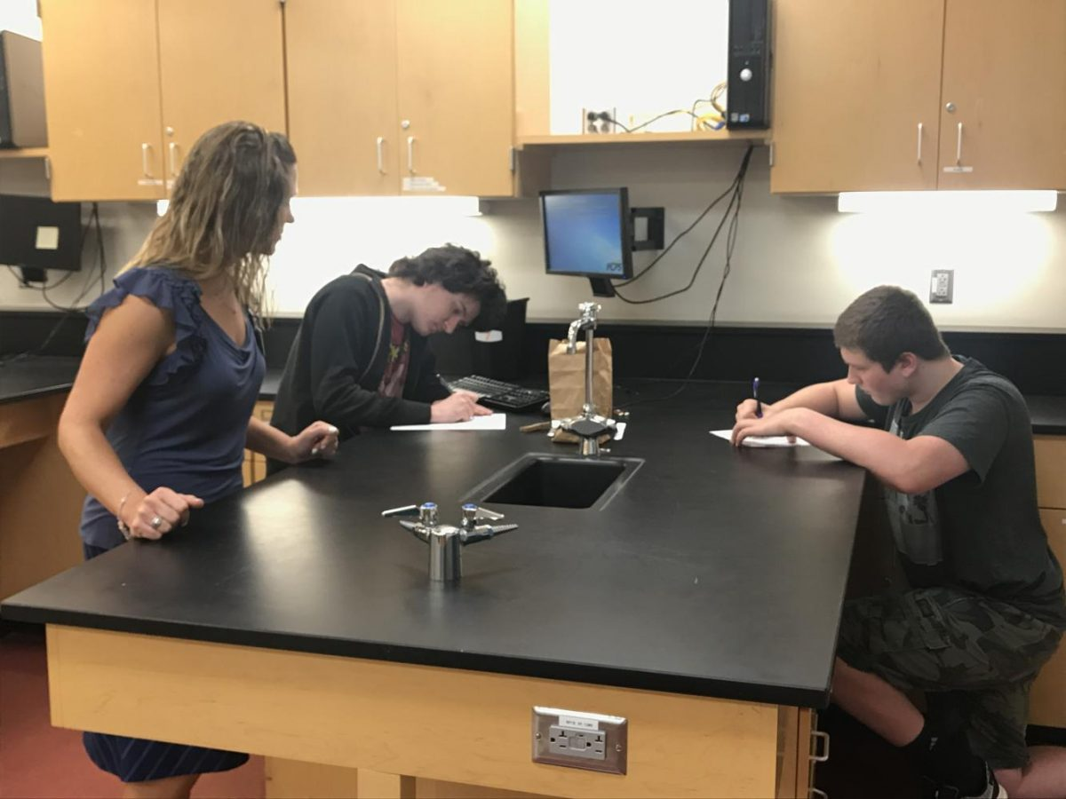 Mrs. Patterson helps her environmental science students Scott Boone and Corwin Verdin with a lab experiment.