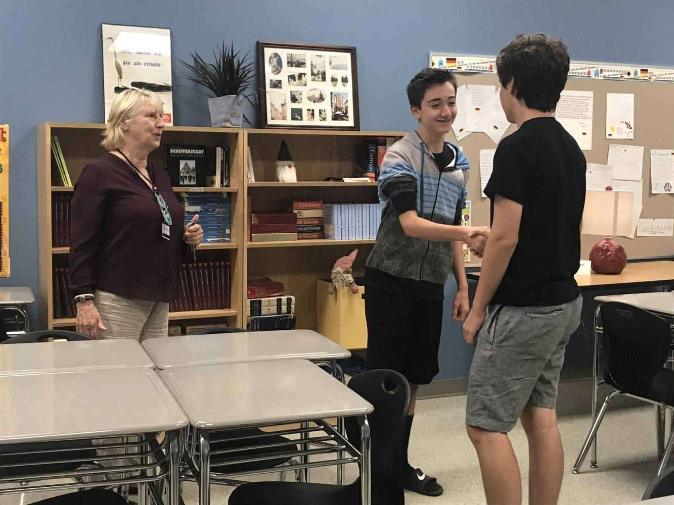 Mrs. Miller teaches German 1 students Max Loggins and Logan Damon how to greet each other in German.