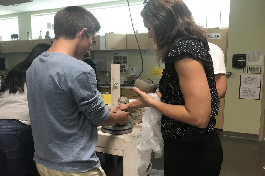 Mrs. Van Horn helps her student, Mark Chaney, with his pottery project.
