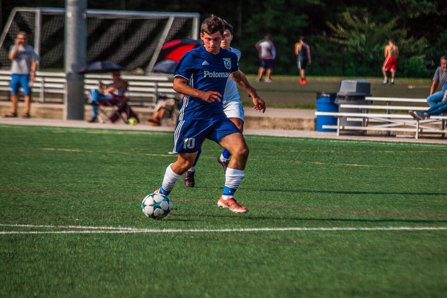 Needle is pictured dribbling the ball down the field during a game for the Potomac Soccer Alliance