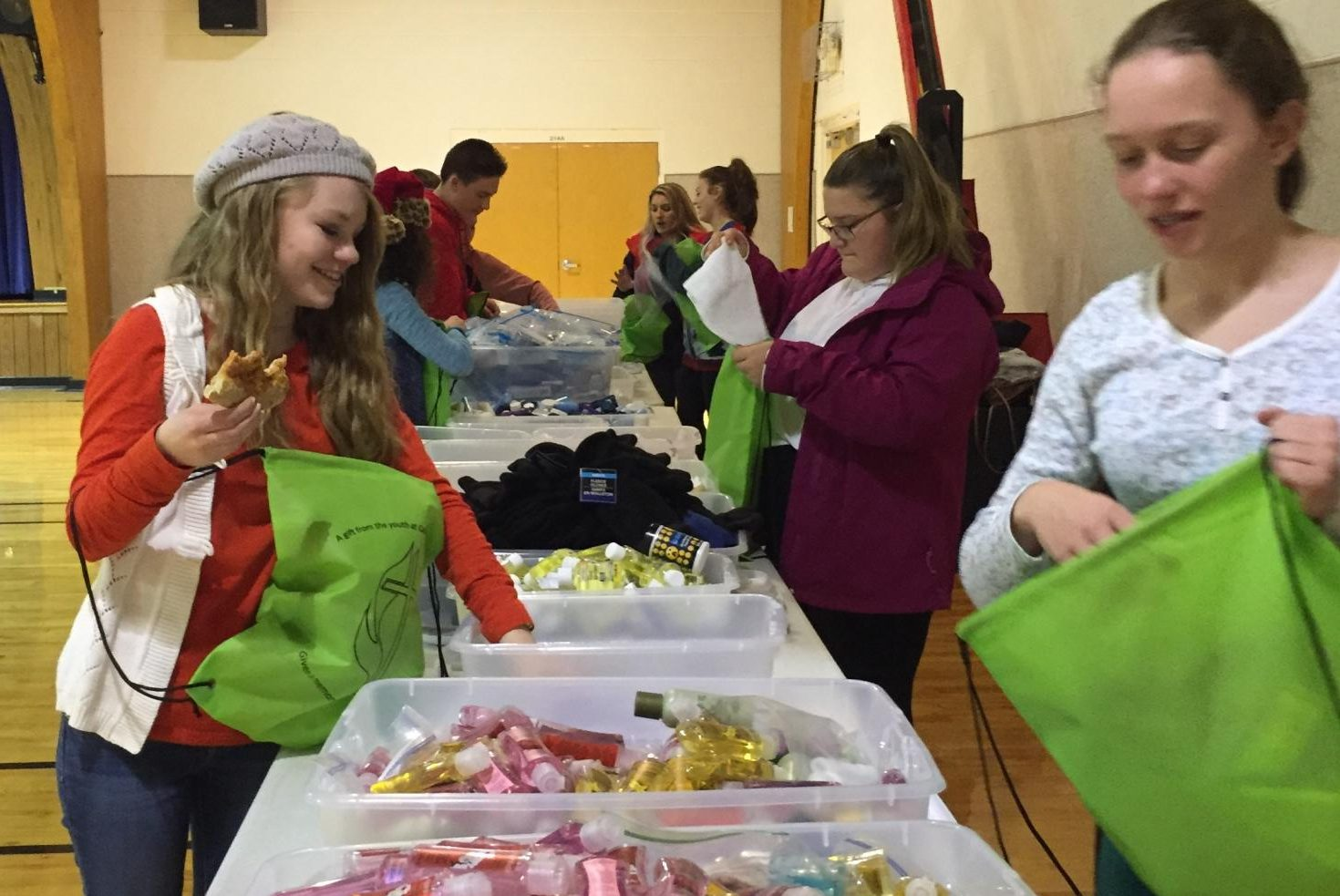 Eighth graders Emily Watson (right) and Christina Damato (left) assemble blessing bags.