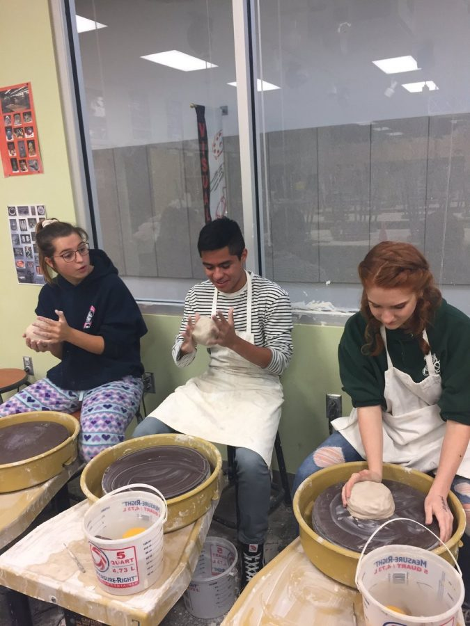 Molly Riegel, Felix Zarate, and Shelby Tkacik make ceramic items for the holiday sale.