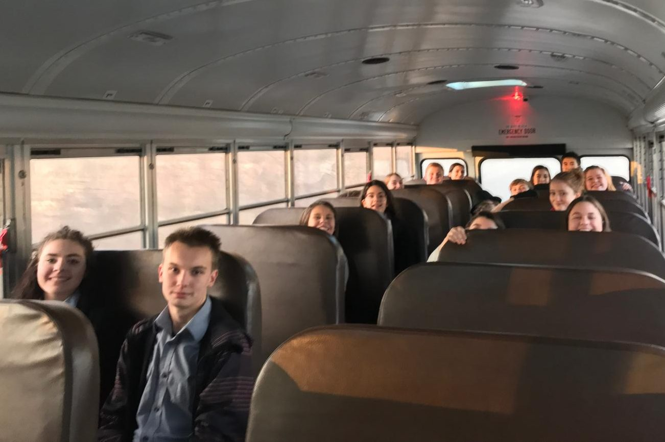 The mock trial team races on the bus to the trial to make it on time.