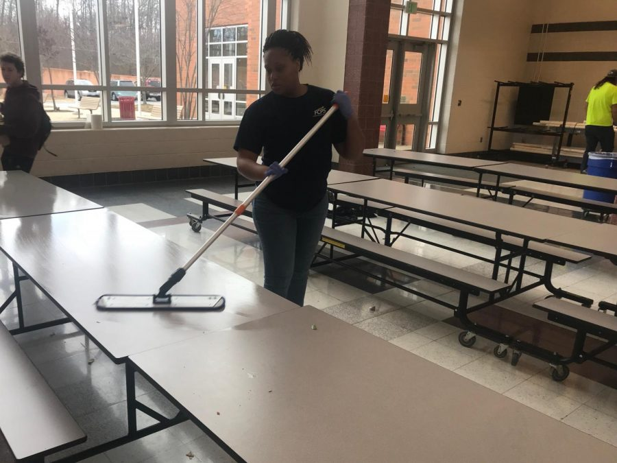 Custodian Shanita Lyles cleans the cafeteria tables between lunch shifts