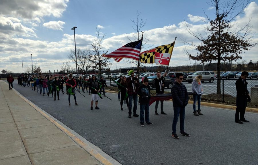 Marching band anticipates step-off in their front parking lot practice.