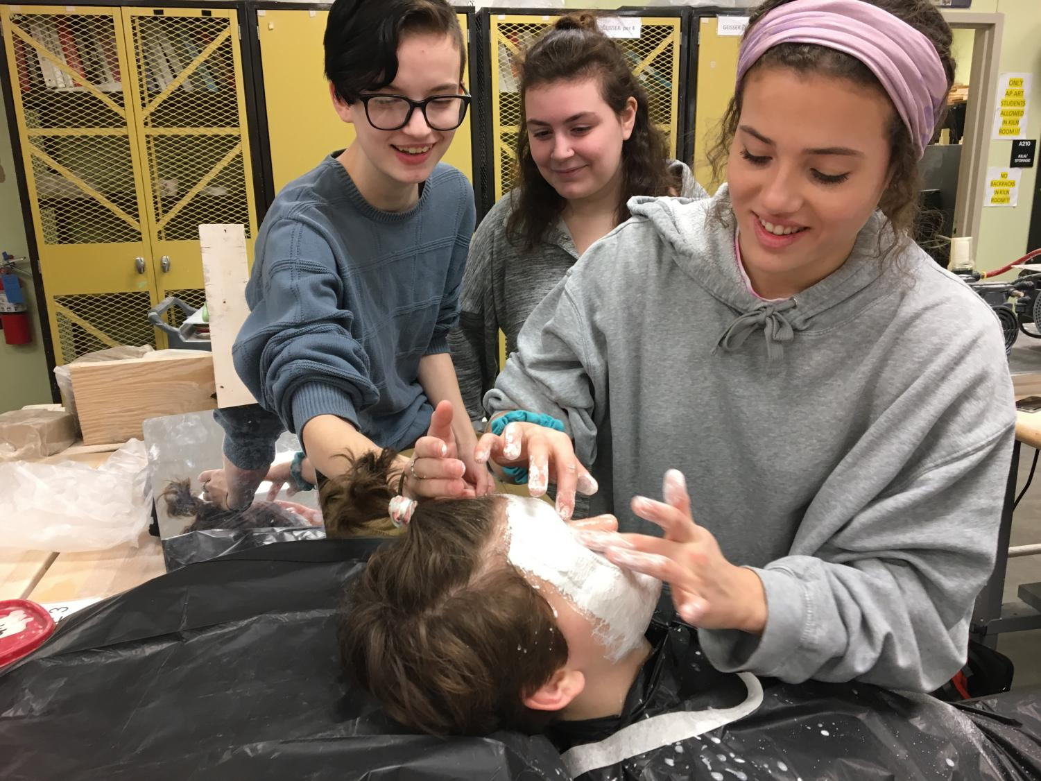 Mary Britton applies face casting to Natalie Roth with help from Kara Roth and Addison Clum.